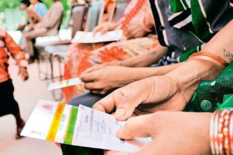 Aadhaar cards held in hands of women used as rep image for Kerala govts Aadhar mandating move