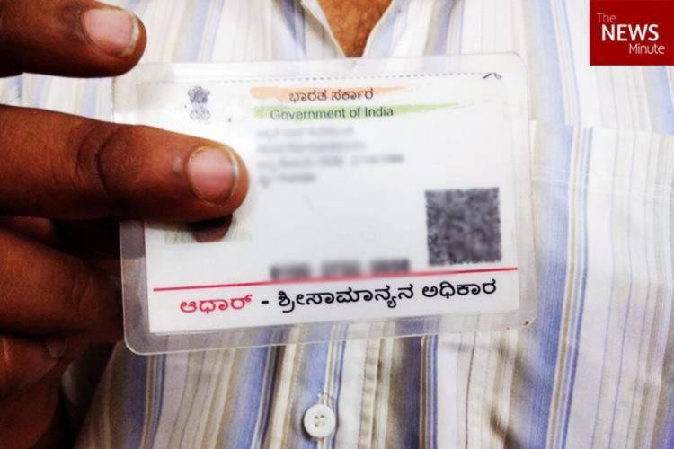 A man holding an Aadhaar card