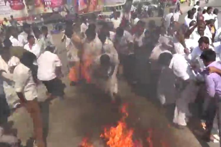 Video AIADMK members veshti catches fire as they burn Vijayakanths effigy