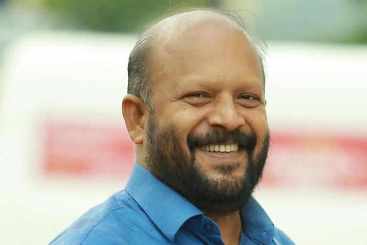 Minister VS Sunil Kumar in blue shirt smiles he has a beard and is slightly bald