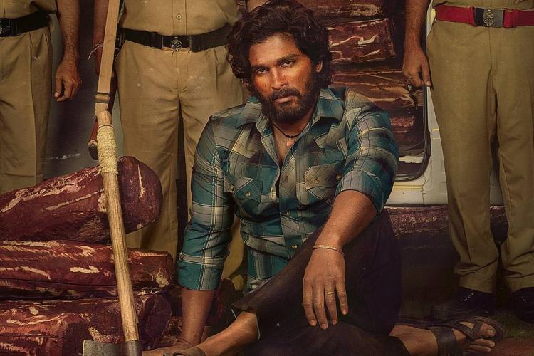 Allu arjun on the poster of pushpa in a blue shirt surrounded by police men with logs of red sanders wood on his right the cops are standing while Allu Arjun is sitting on the floor with his left arm resting on his left knee and staring into the camera