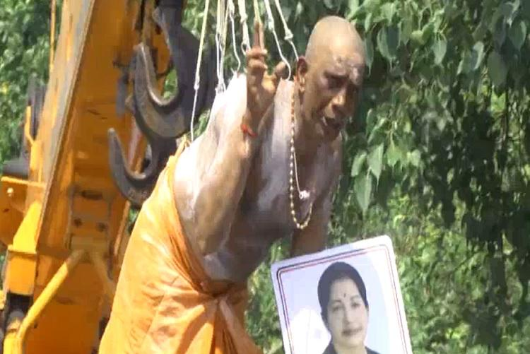 Amma worship reaches painful heights Man hangs on hooks from crane as prayer