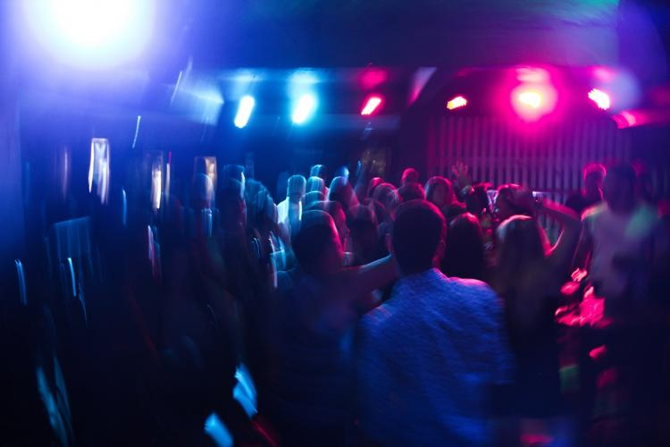 People dancing at a rave party with blue and pink lights the picture appears blurry