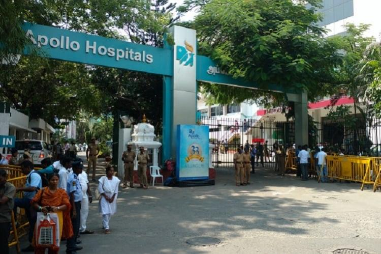 A crowd of people standing outside an Apollo hospital