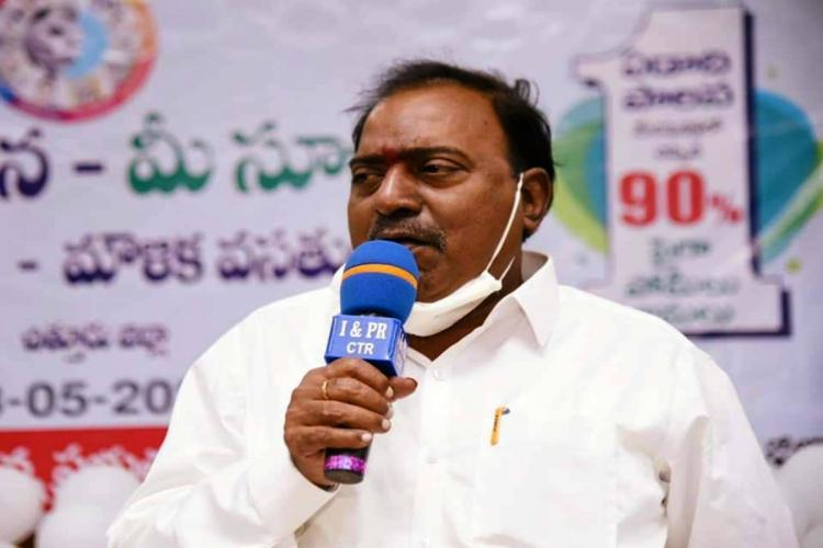 Tirupati MP Balli Durga Prasad Rao is seen addressing a gathering He is wearing a white shirt with his mask pulled down on his chin He is holding a blue-coloured mic
