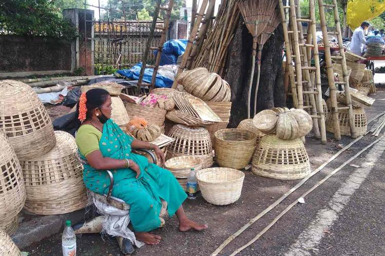 Medha tribal woman in green saree sitting with bamboo products