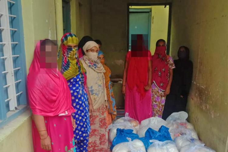 Women standing around ration kits provided by Bangalore Pledge Project