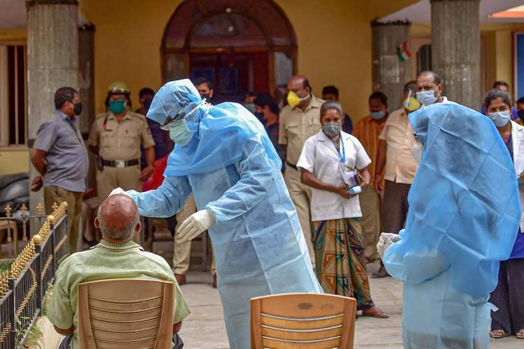 A health worker in PPE suit collecting nasal swab samples from a man for coronavirus test