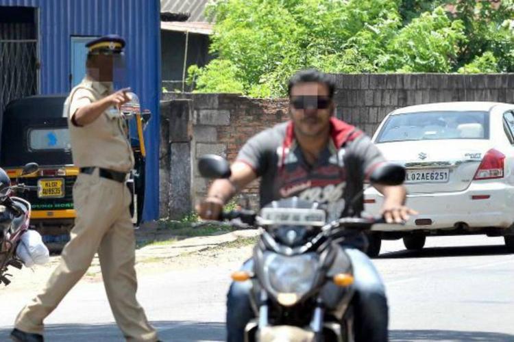 A policeman recording helmet less riding