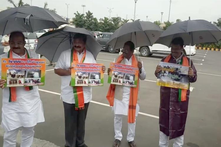 Andhra BJP MLAs come in raincoats hold umbrellas to protest water leaks in Assembly