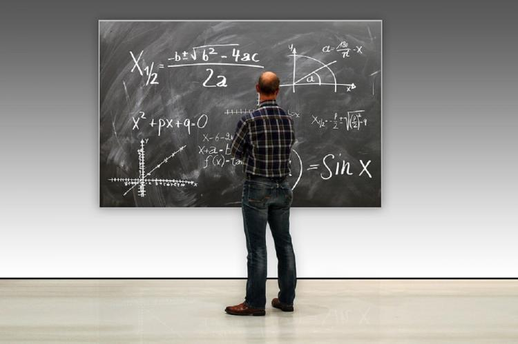 A proffessor looking at the black board