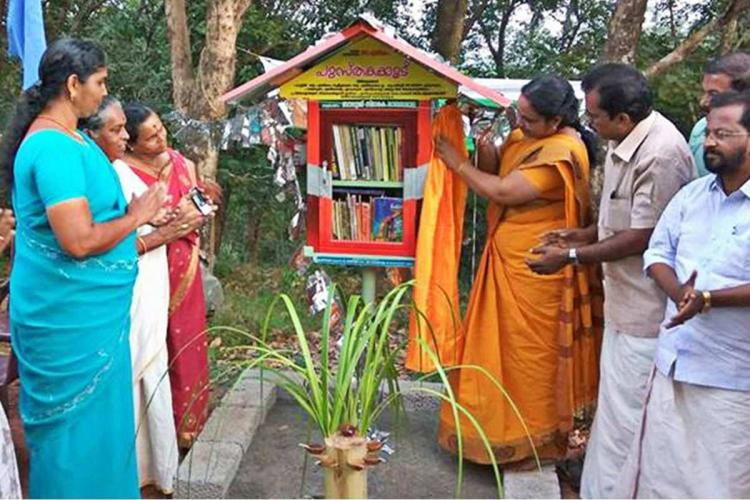 Men and women stand around a little box of books set up in the village of Perumkulam