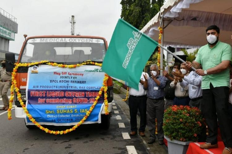 Collector Suhas in green waves a green flag as others watch in front of a truck which has a banner saying liquid oxygen