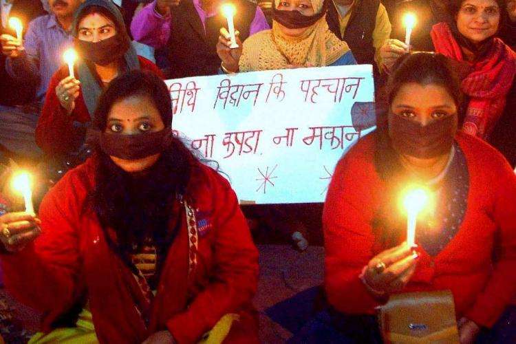 Two women at a candle light protest seen holding two candles