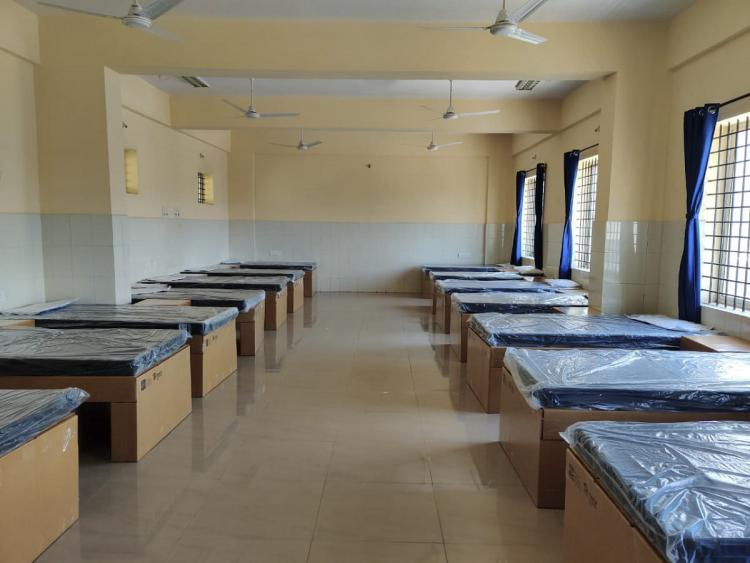 an empty covid care centre with beds