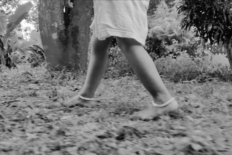 Two legs of a toddler wearing anklets and running across a field in a black and white picture