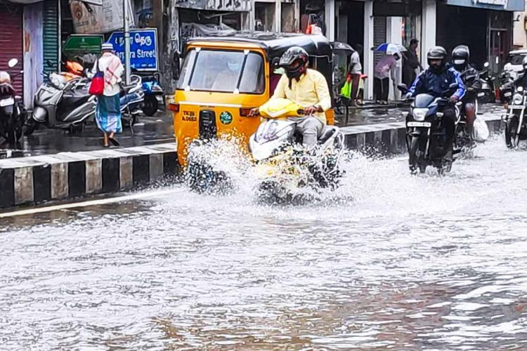 Auto and bikes on Chennais water logged road