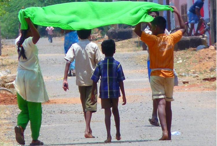 Four children one girl and three boys playing on the road under what seems to b a green dupatta