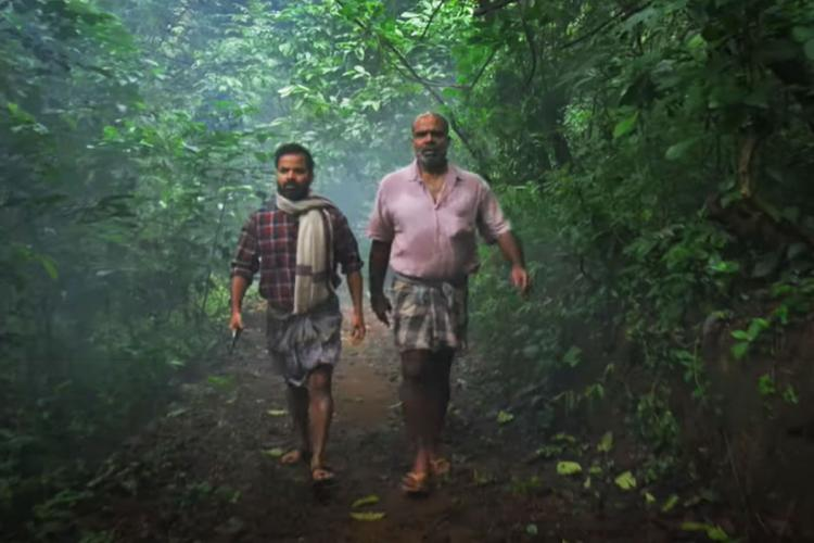 Vinay Forrt and Chemban Vinod walk through woods in a still from the Malayalam film Churuli