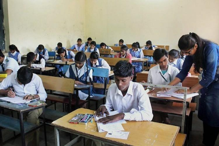 Students writing exams while teacher monitoring