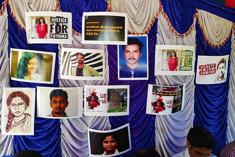 At a protest for Fathima a backdrop tells the story of institutional discrimination