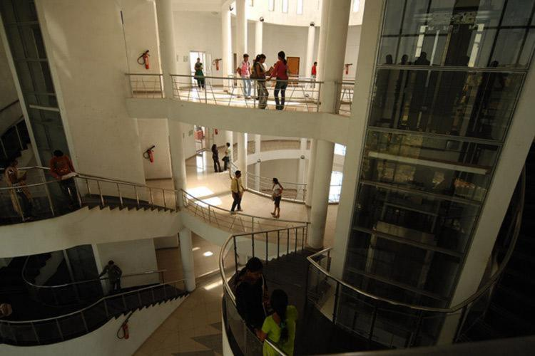 Inside a college where students are seen on various floors and long staircases