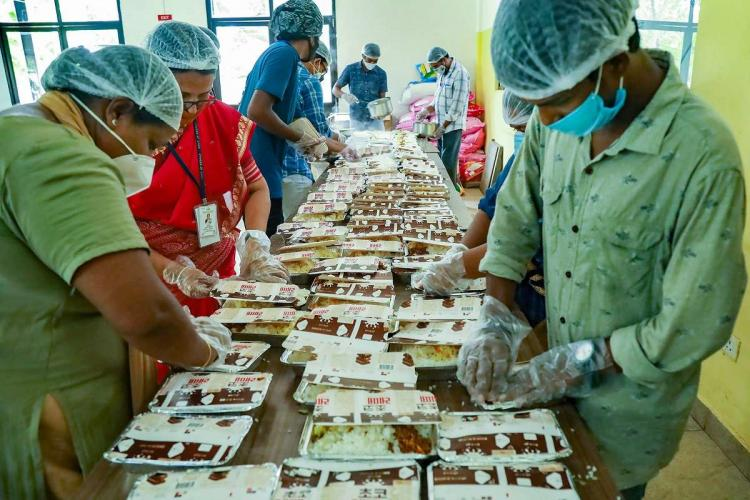 Volunteers pack food for COVID-19 patients at a community kitchen in Kozhikode Kerala during COVID-19 lockdown