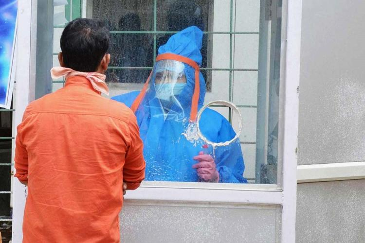 A health worker in blue PPE kit takes testing sample of a person