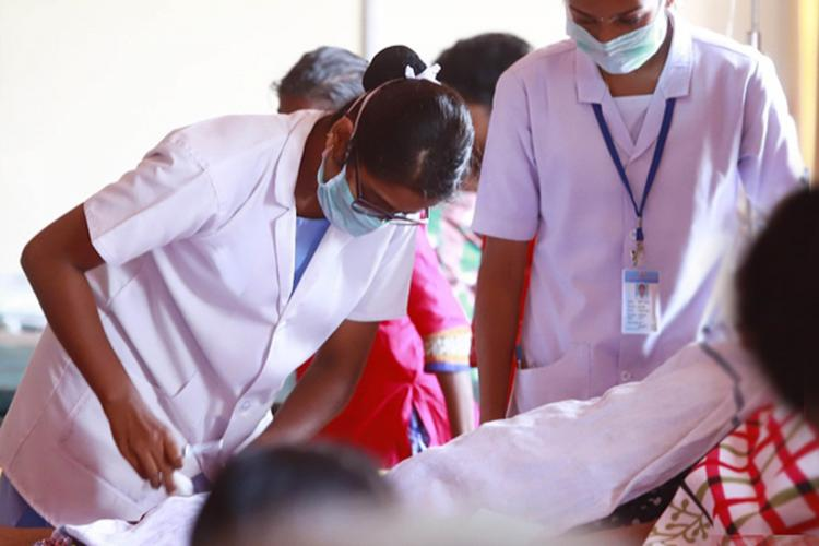 A nurse in a coronavirus ward with other people wearing a mask