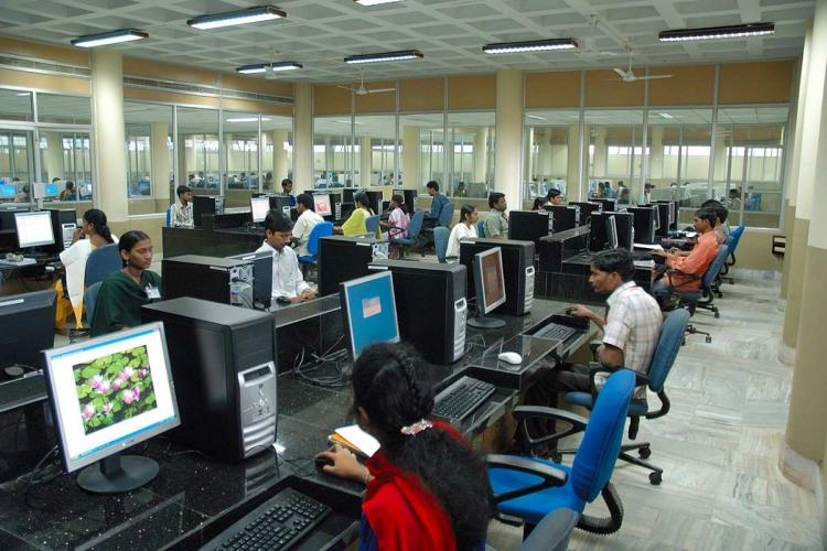 An office room where employees are sitting in front of their computers in multiple rows arranged across a large hall