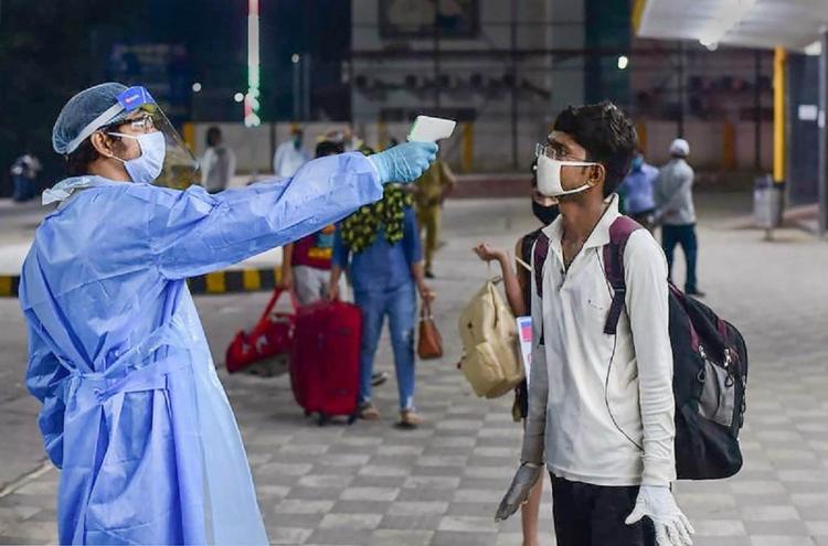 Medics conduct thermal screening of passengers before boarding a train at Prayagraj Junction