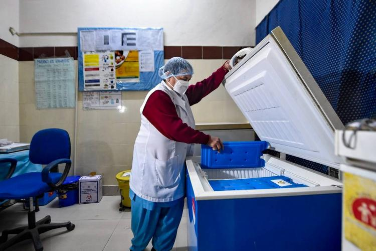 A woman health worker looking at COVID-19 vaccine cold storage