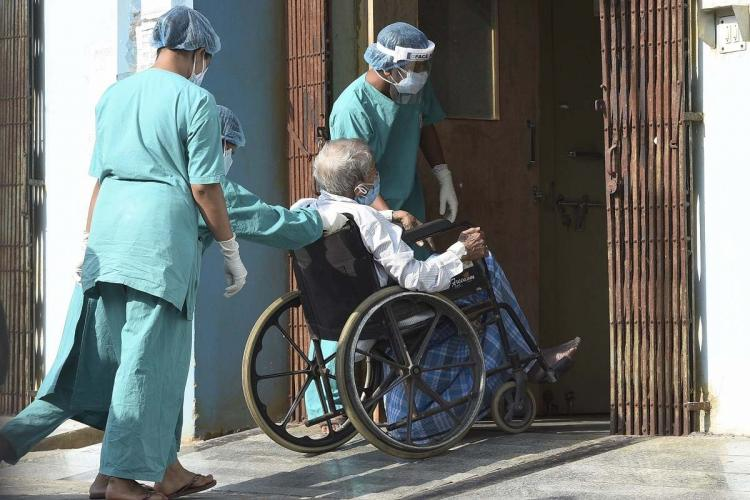 Healthcare Workers in green uniform moving a patient in a wheel chair inside a hospital