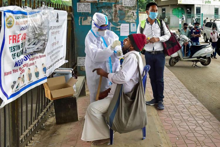A health worker wearing PPE kit collects samples for COVID-19 tests at a market in Bengaluru