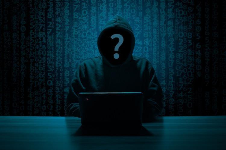 Anonymous cyber fraud sitting infront of a computer