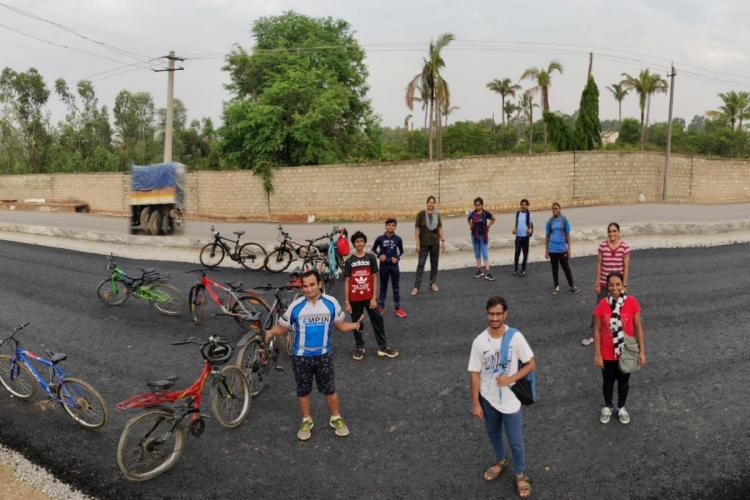 Bengaluru cyclists after a long ride standing in a circle with their cycles forming a figure 30