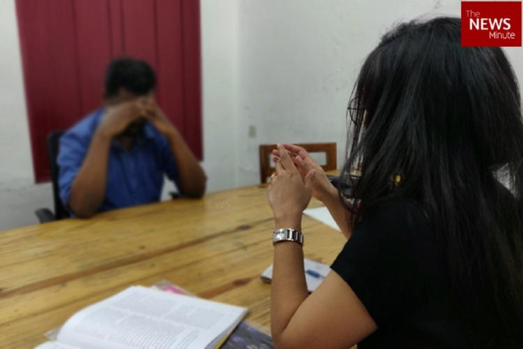 A man sitting across a woman with his hands covering his forehead hiding his face
