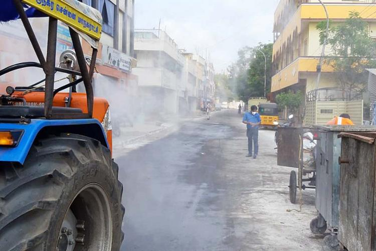 A street in Chennai being disinfected as a man wearing mask walks by