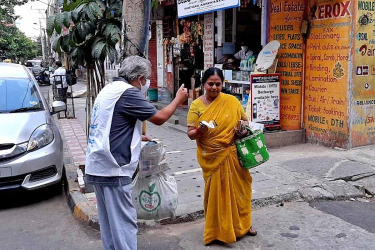 a man gives a woman without a mask one cloth mask on loafer lane in vasanthnagar bengaluru