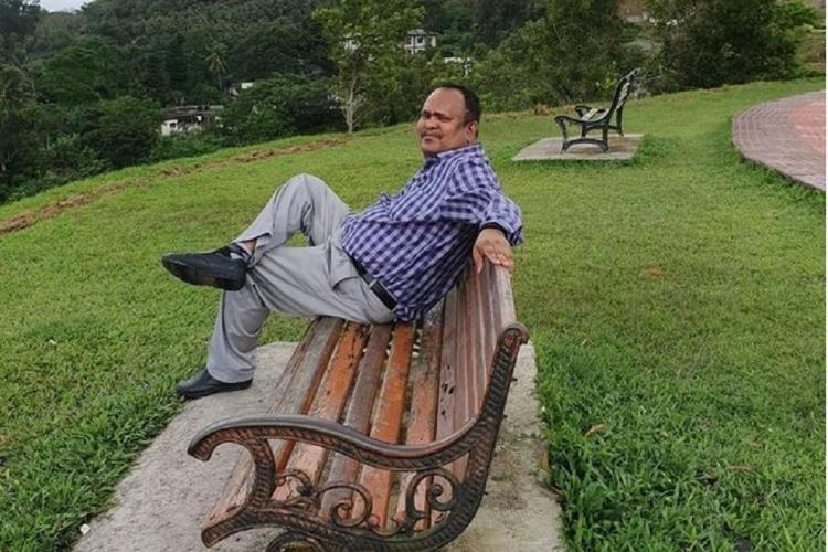 File photo of Chennai neurosurgeon Dr Simon Hercules sitting on a bench cross-legged in a park