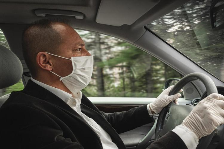 A middle-aged man wearing a suit and a mask with gloves is driving a car