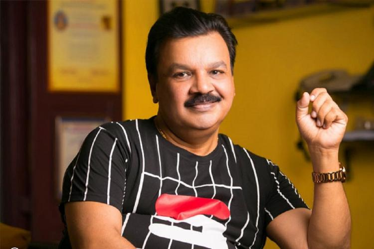 Edavela Babu in a black t shirt sits smiling with his left hand raised up against a background of yellow walls