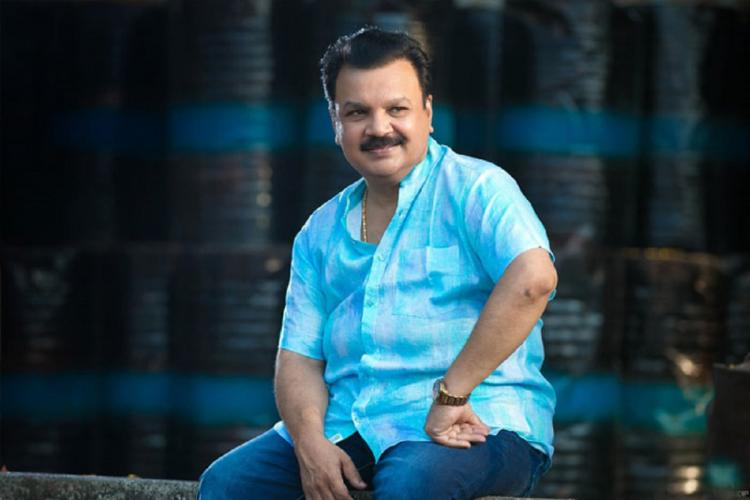 Edavela Babu wearing a blue shirt sits with one hand on his hip and smiles