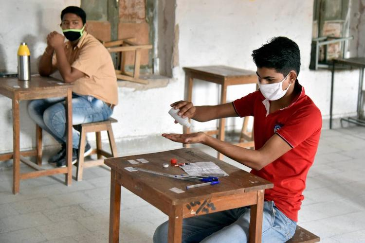 A student sanitises his hands while appearing for an exam amid coronavirus pandemic