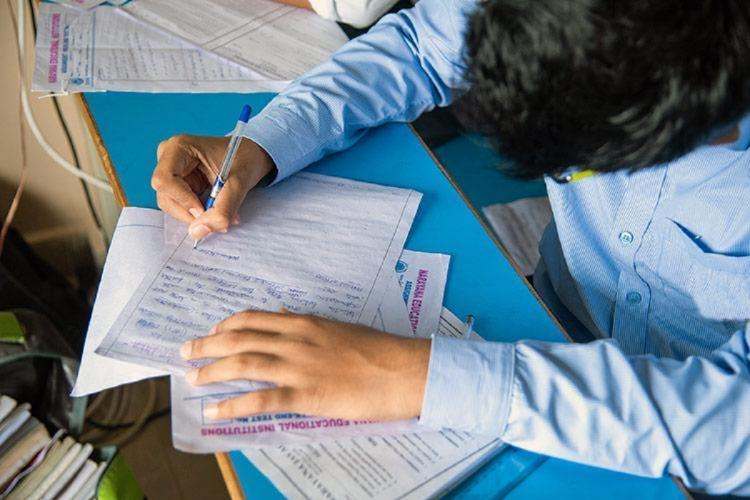 Student in a blue uniform writing exam