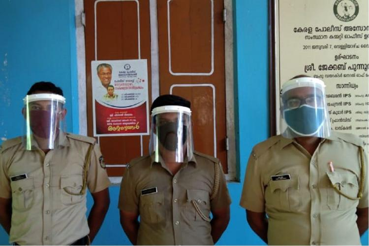 Three police men stand at a station wearing their uniforms with face shields for protection against coronavirus
