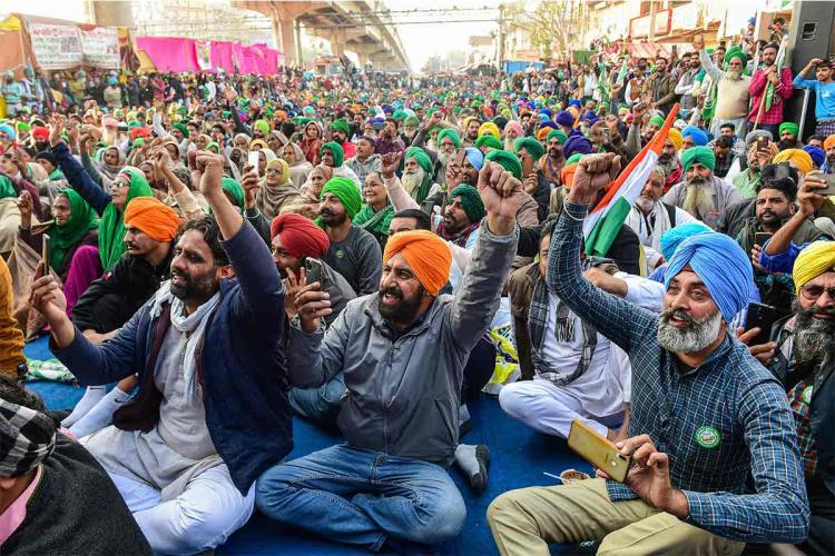 A visual from the farmers protest with three of them holding up their phones