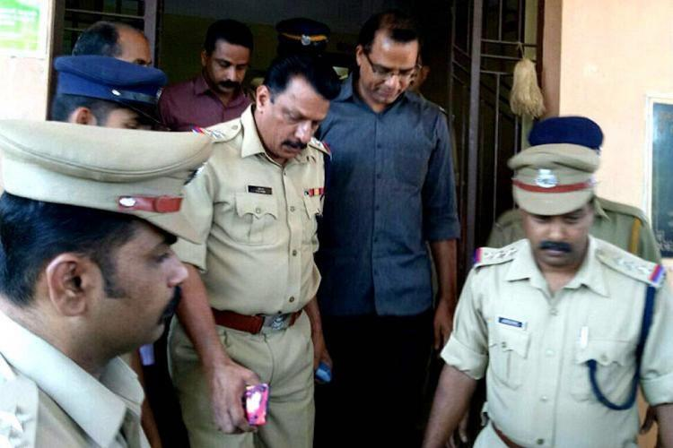 Rape convict priest Robin Vadakkumchery being brought out of court by four policemen