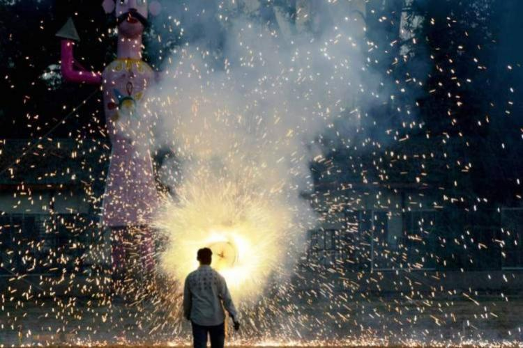 A man in a white shirt watches as firecrackers go off His back is to the camera