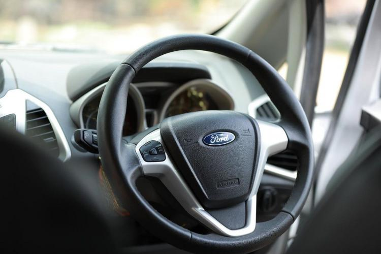 A steering wheel of a car with Ford logo